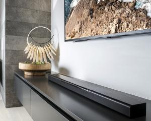 Sound bar on a cabinet below a flat screen tv.