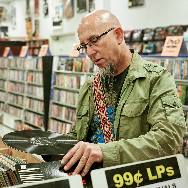 Man in record store looking at a vinyl record.