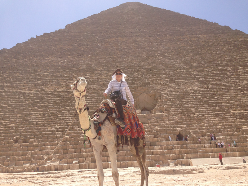 Young man riding a camel in front of a pyramid.