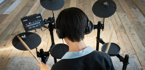 Young man playing electronic drums with headphones.