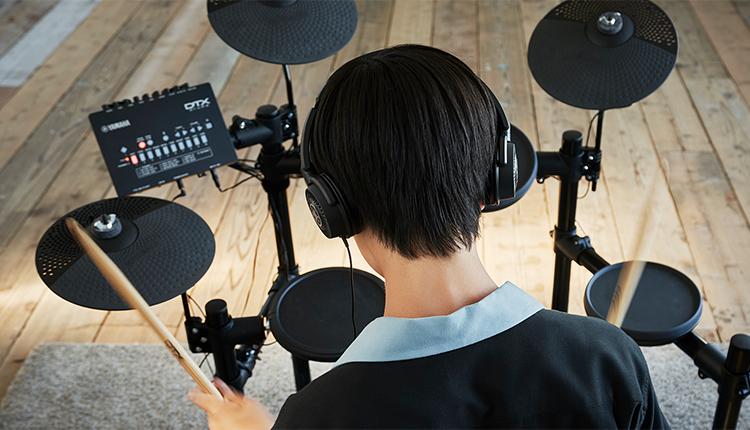 Young man playing electronic drum set.