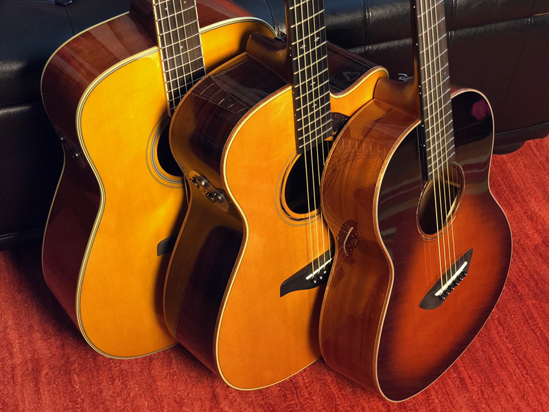 Three acoustic guitars lined up from left to right largest to smallest.