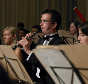 Man playing oboe in an orchestra.