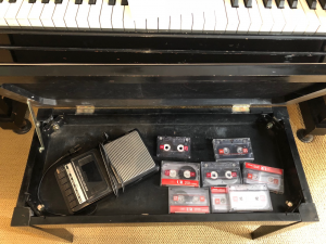 Interior of a piano bench showing a portable cassette player and cassettes.