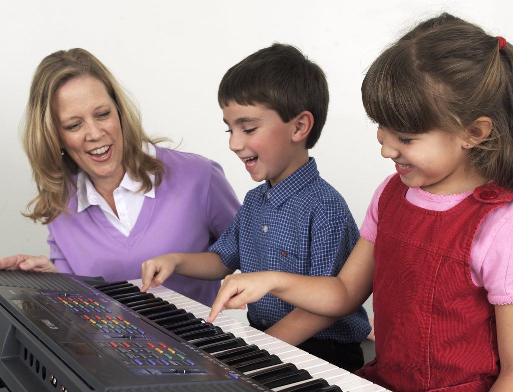 Woman watches as two young children play the keyboard.