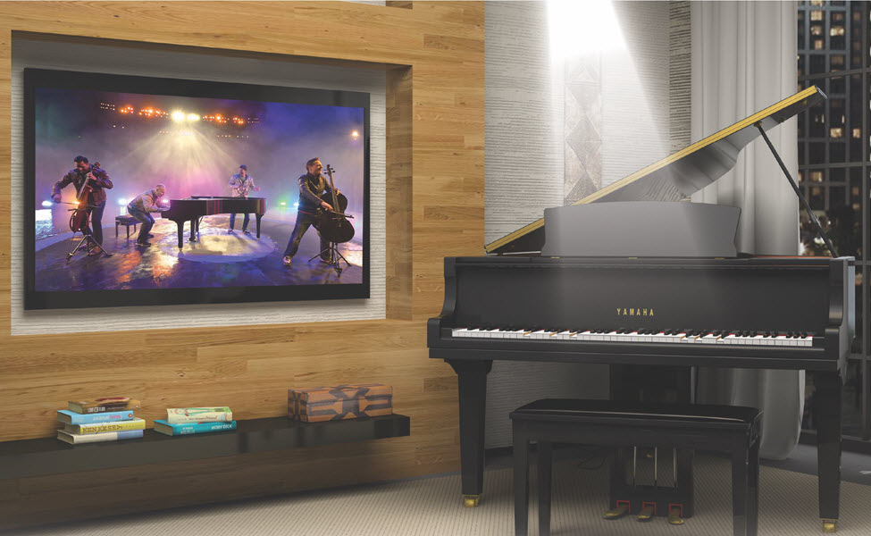 Musicians performing in video on big screen tv on wall in living room while modern player piano in room is accompanying.