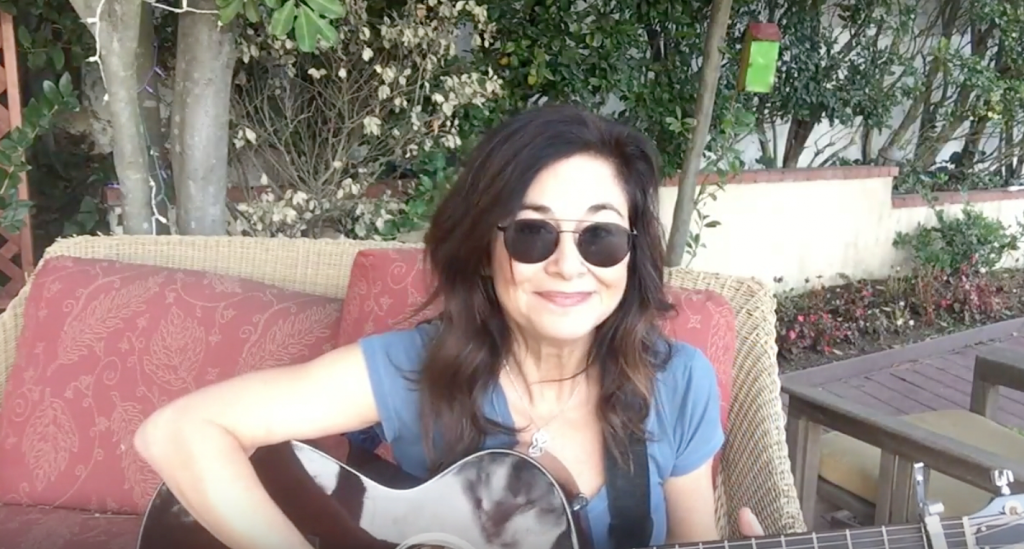 Songwriter Shelly Peiken on her patio in sunglasses playing her guitar.
