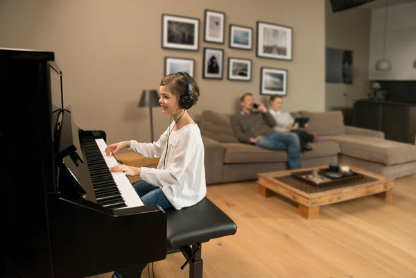 Young girl practicing the piano in the living room with a headset on while her parents are relaxing in background talking on mobile and working on a tablet.