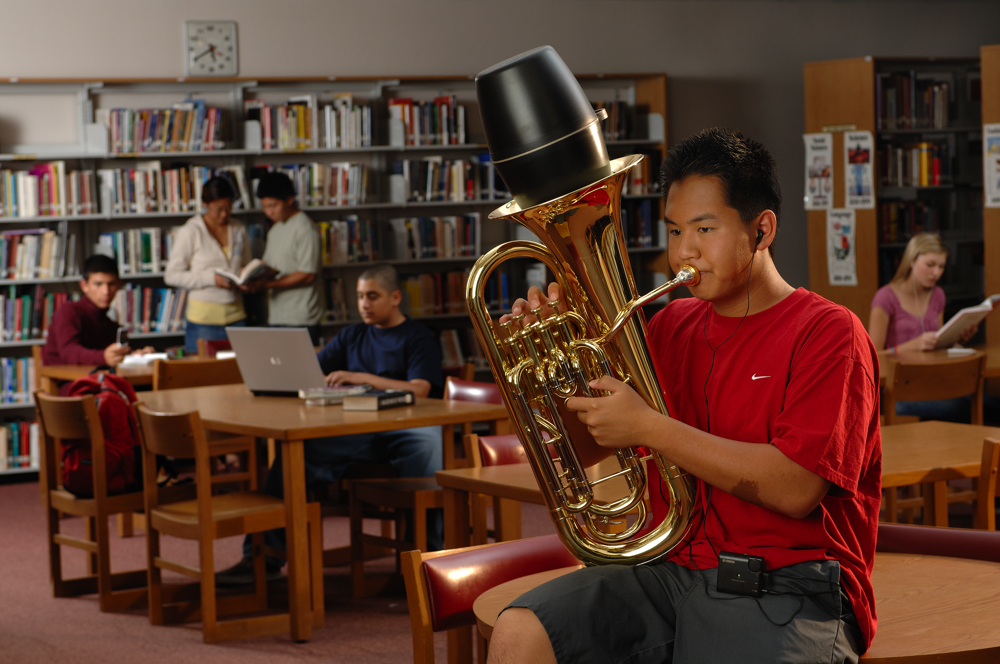 Young man in a school library playing a tuba with a large mute inserted in the bell and he is wearing wired earbuds to a small device on his belt while a group of other students and the library are focused on their work in the background.
