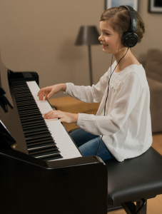 Young girl playing piano while wearing headphones.