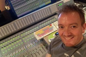 Man in his 30's dressed in t-shirt and smiling for the camera while sitting in front of a sound studio audio console.