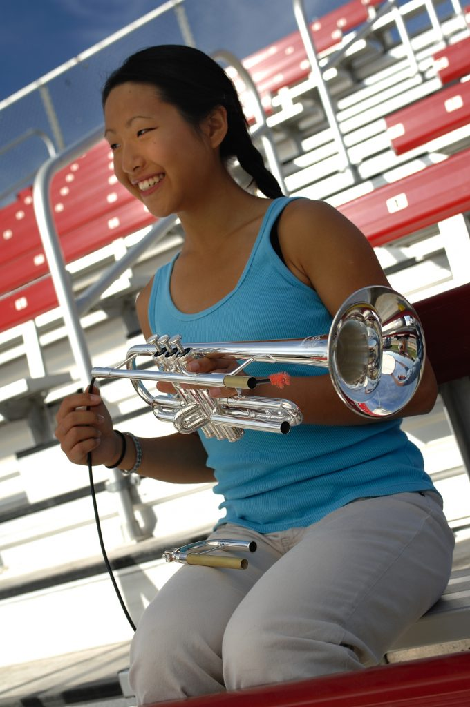 Young woman sitting in empty stands cleaning a trumpet.