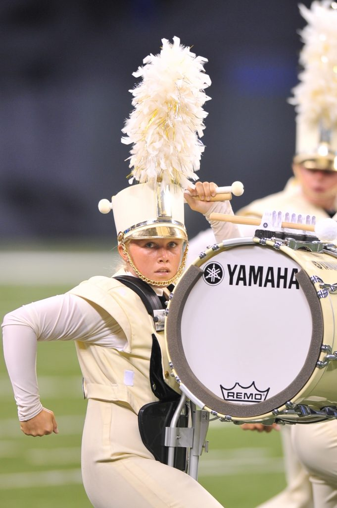 Young woman in marching band uniform playing bass drum.