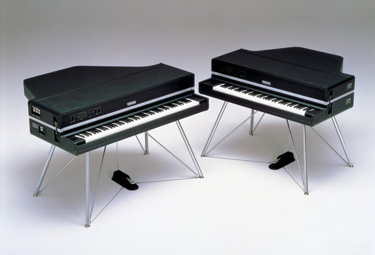 Two electronic pianos that look like small grand pianos on metal legs.