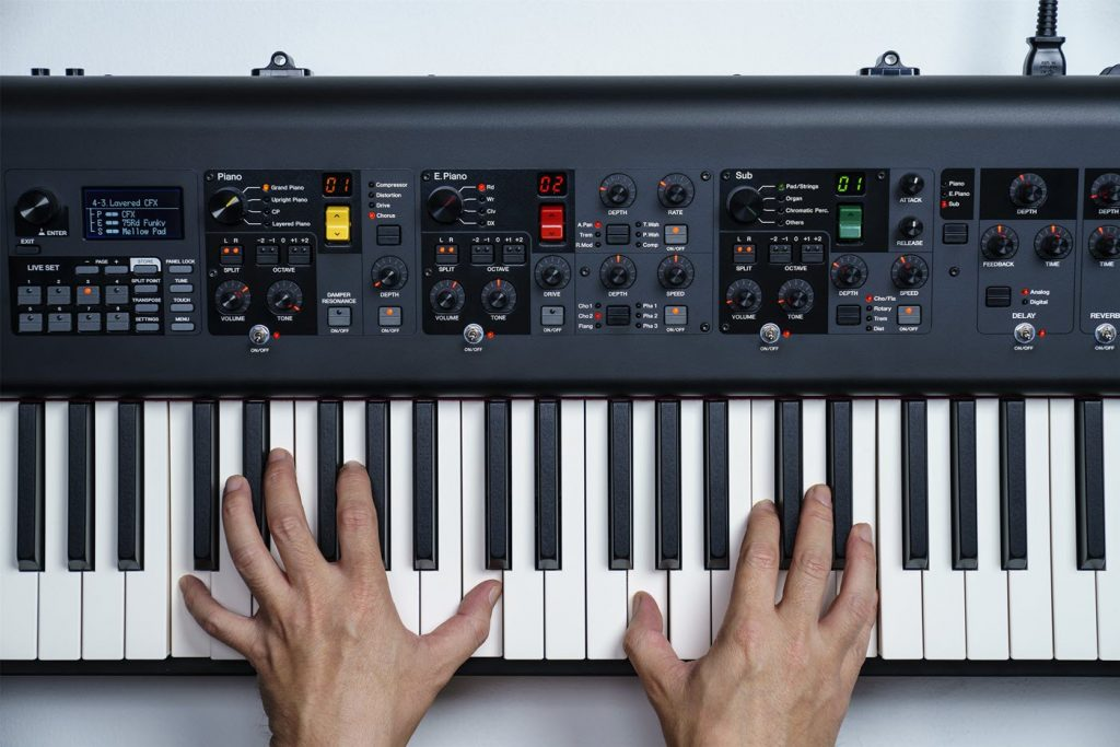 Two hands playing an electronic keyboard.