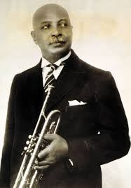 An African American man in a suit and tie holding a trumpet.