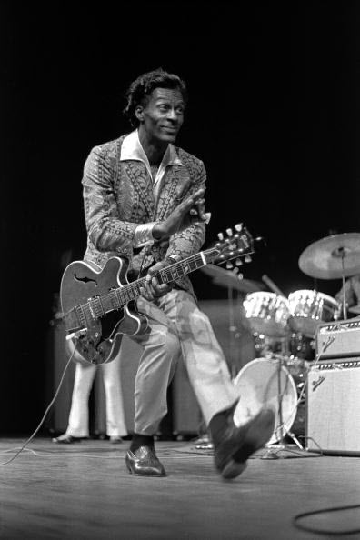 African American man in white pants and sports jacket with an electric guitar duckwalking across a stage with other musicians and drums in background.
