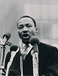 Dr. Martin Luther King speaking behind four news microphones.