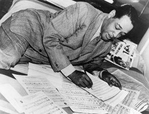 Tall African American man in a windowpane patterned suit and tie laying on his side on a bed while writing out musical notation.
