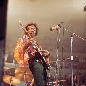 African American man in psychedelic printed shirt open over a t-shirt and jeans wearing a headband across his forehead holding his hair out of his eyes while he plays the electric guitar.