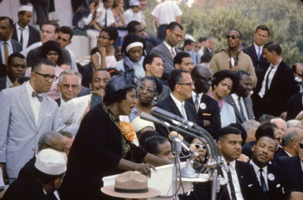 Mature African American woman in coat and hat speaking into a group of microphones at an outdoor event with approximately 30 men in suits in background.