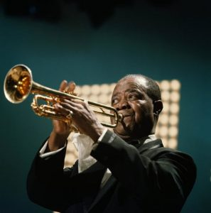 Middle-aged African American man in a suit onstage playing a trumpet.
