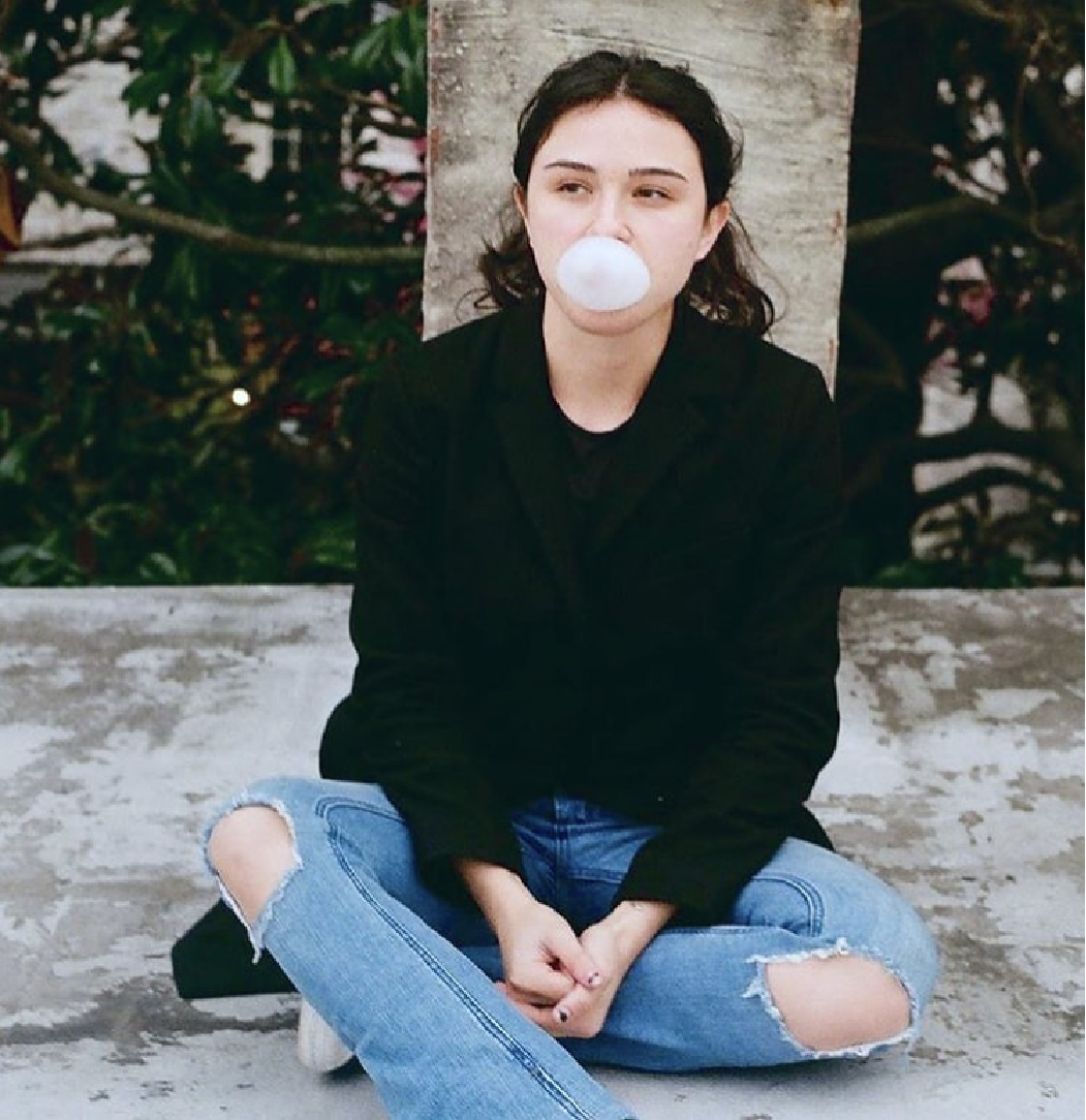 A girl with ripped jeans on leans against a pole. She is blowing a bubble with bubble gum.