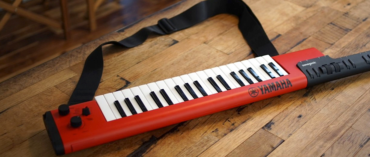 An image of a keytar. It is a portable keyboard that can be held and played like a guitar. There is a strap attached to it.