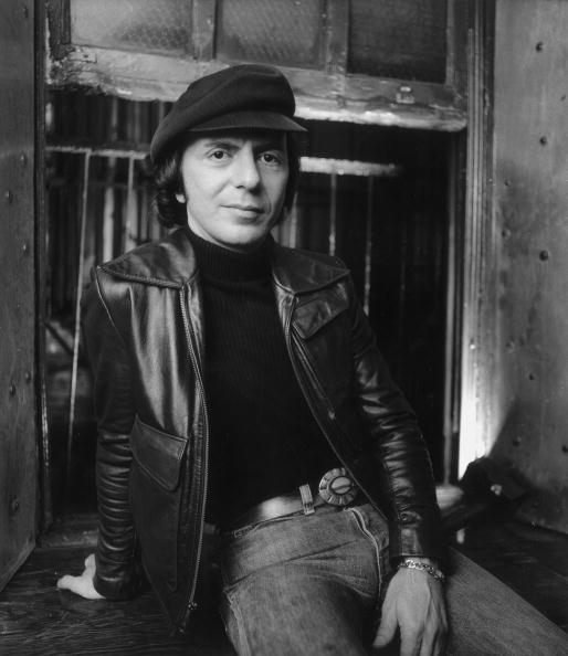 Man in turtleneck, belted jeans, leather jacket and cap.
