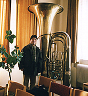 An man standing next to a tuba that is twice as tall as he is.