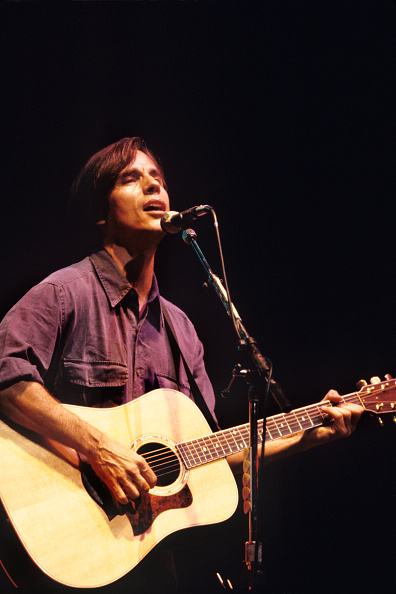 Man in casual clothing on stage singing and playing acoustic guitar.