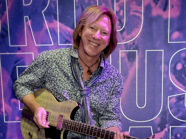 Robbie Calvo in patterned casual shirt and scarf smiling at camera while playing his electric guitar.