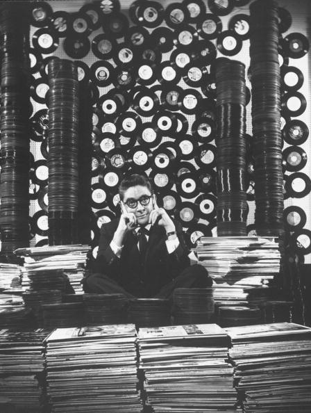 Man in suit and glasses sitting surrounded by stacks of vinyl records and stacks of album covers.