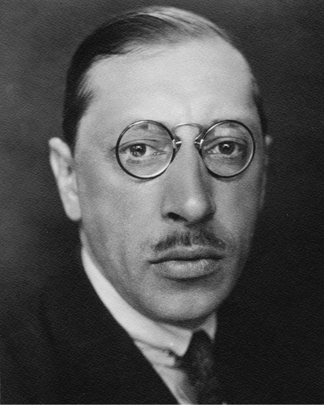 An image of Igor Stravinsky, a man with a melancholic expression and round glasses.