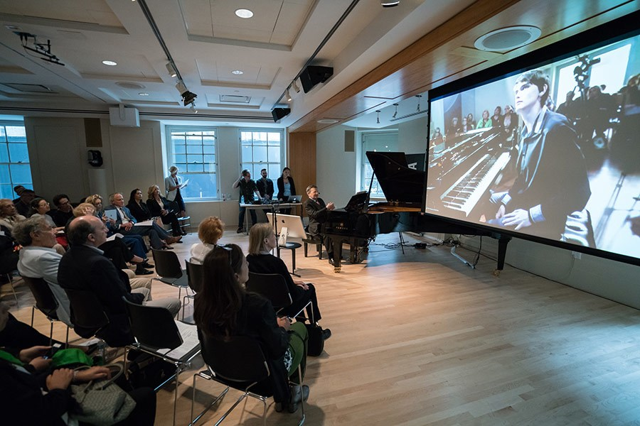 A group of people watch a presentation by a pianist in a large room with a projector.