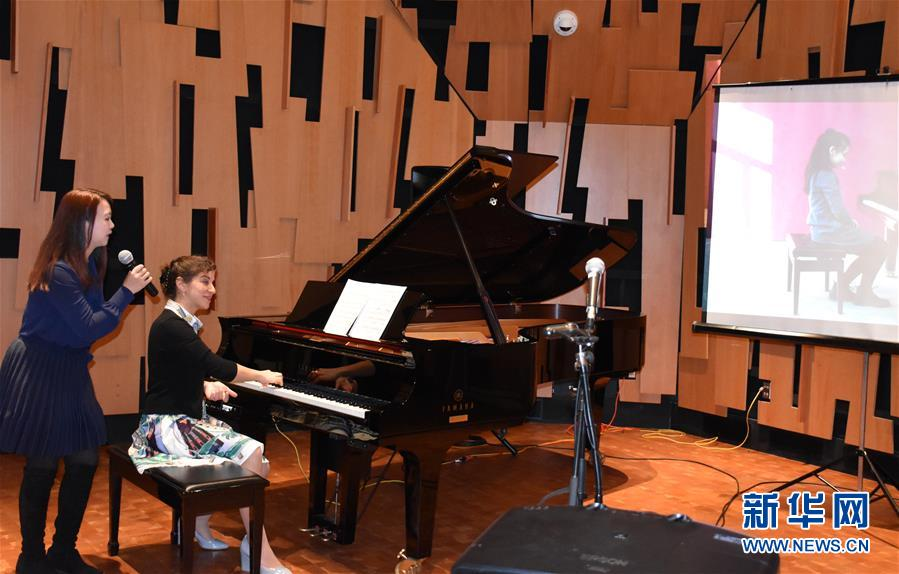 An image of a person playing a piano while someone stands behind her with a microphone.