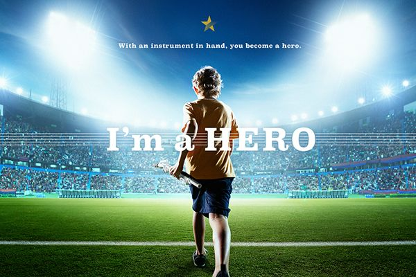 """An image of a child standing in front of a stadium with lights in front of him. Text overlay says """"I'm a hero."""""""