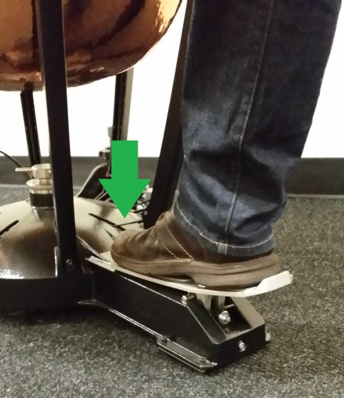 A foot pressing down on a pedal attached to a timpani