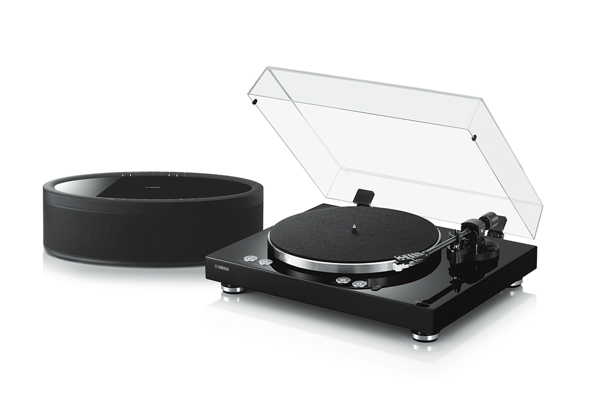 An image of a turntable next to a high-quality speaker.