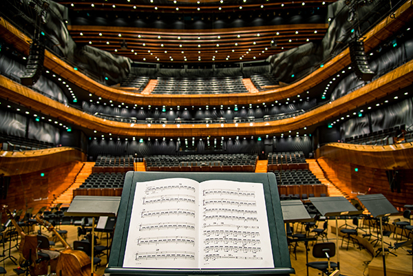 An image of a musical note sheet set up in front of a concert hall.