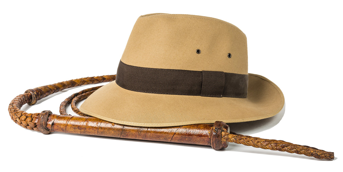 Fedora hat and bullwhip isolated on white background.