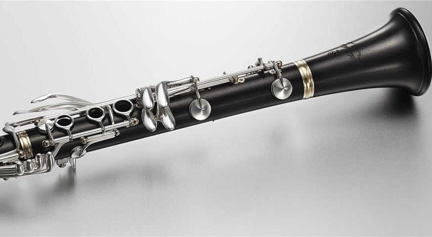 Closeup of a portion of a wooden clarinet on flat surface.