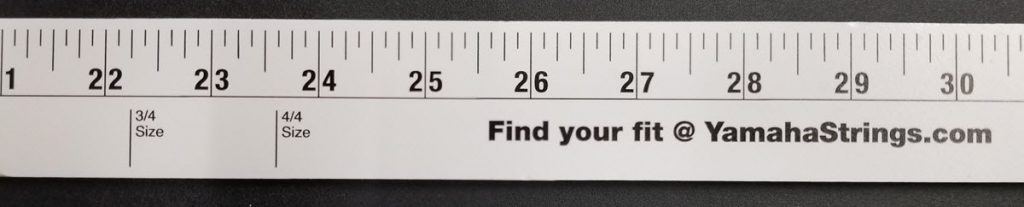 "Closeup of measuring tape with not only the usual inches and portion of an inch marked, but also marks for 3/4 size and 4/4 size as it pertains to violins. The words ""Find Your Fit @ YamahaStrings.com"" is also displayed on the tape."