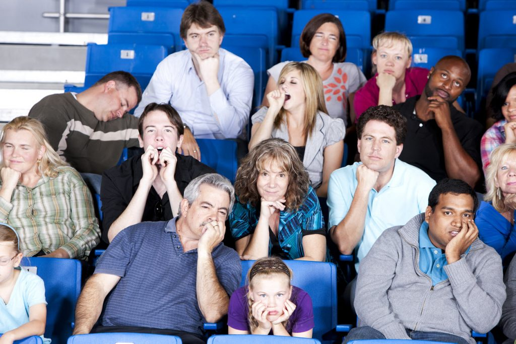 A group of people in stadium seats yawning, sleeping resting heads on hands with expressions of boredom.