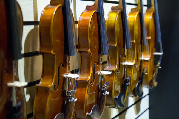 Row of violins hanging on a wall.