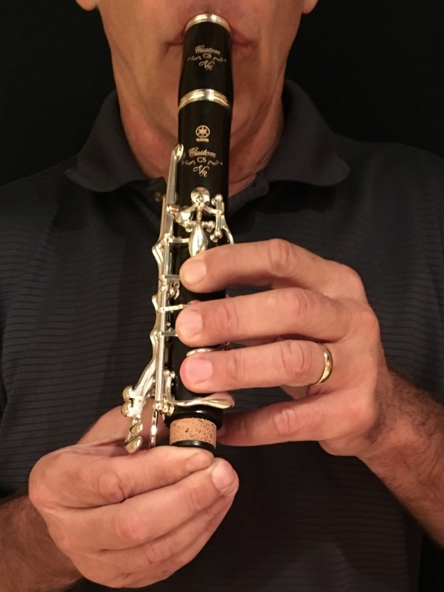 Close-up of man blowing through a disassembled clarinet.