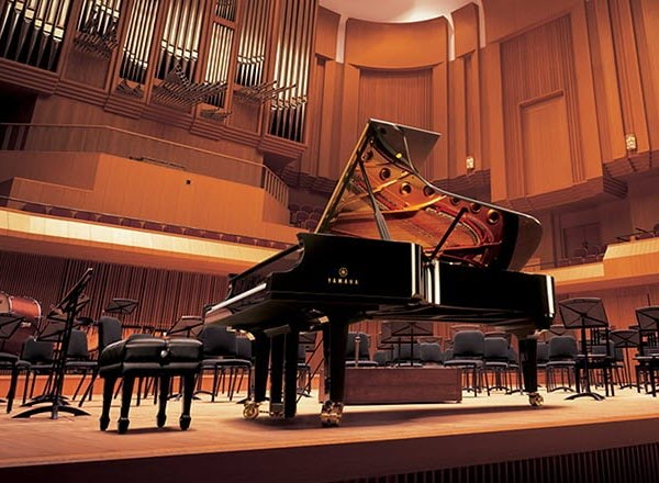 Yamaha Disklavier Concert Grand Piano on a concert hall stage set for performance.