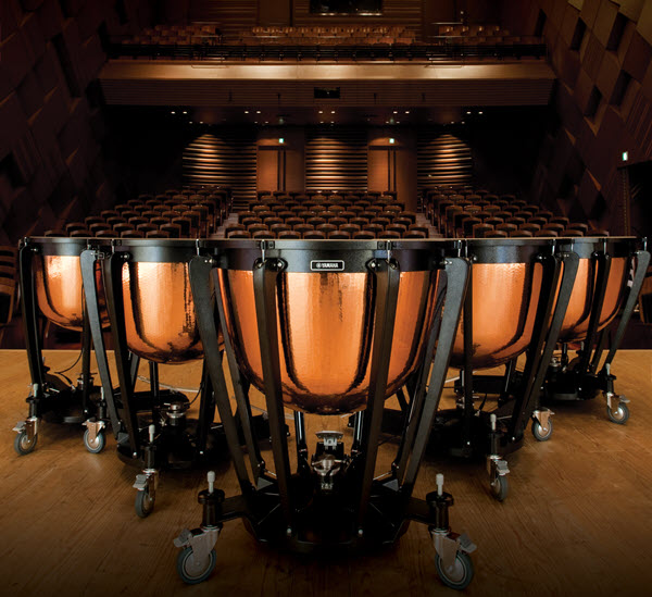 Collection of timpani on a stage in an empty theater.