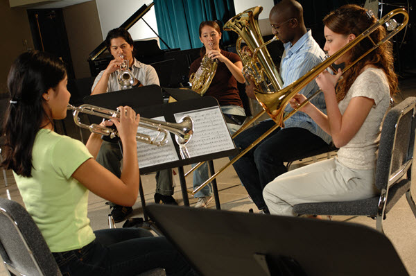 Five young people practicing as brass quintet in a practice room.