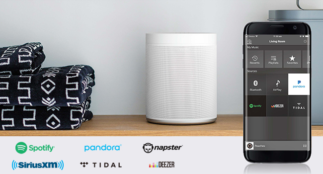 Small speaker on a shelf with towels adjacent plus a smartphone in the foreground showing an app screen.